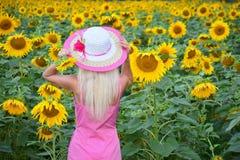 De mooie vrouw in een hoed op het gebied van zonnebloemen Royalty-vrije Stock Foto