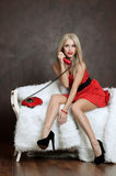 De mooie vrouw in een rode kleding met oude telefoon Stock Foto