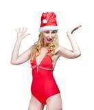 De mooie vrouw in een rood badpak en een rood GLB van Santa Claus stock foto