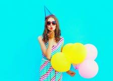 De mooie vrouw in een verjaardag GLB is verzendt een luchtkus houdt een lucht kleurrijke ballons op blauwe achtergrond Royalty-vrije Stock Fotografie