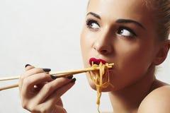 De mooie vrouw eet noodles.red-lippen. Chinese stokken. snel voedsel royalty-vrije stock foto
