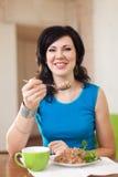 De mooie vrouw eet boekweit Stock Foto's