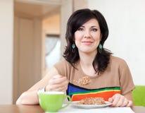 De mooie vrouw eet thuis graangewas Stock Foto's