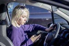 De mooie vrouw gebruikt een slimme telefoon binnen de auto royalty-vrije stock fotografie