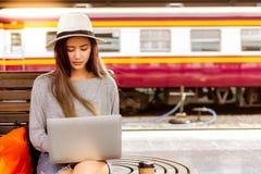 De mooie vrouw gebruikt laptop bij station alvorens mooie Aziatische vrouwenreis aan bestemming te charmeren Zij is een blogger e stock foto's