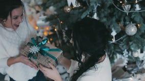 De mooie vrouw geeft aanwezige Kerstmis aan zijn meisje stock videobeelden