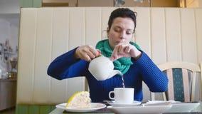De mooie vrouw giet thee van een theepot in een kop in koffie stock footage