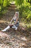 De mooie vrouw ging zitten op een bosvoetpad, daling Royalty-vrije Stock Foto