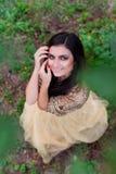 De mooie vrouw in gouden kleding glimlacht en koestert zich Royalty-vrije Stock Afbeeldingen