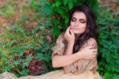 De mooie vrouw in gouden kleding slaapt en koestert zich Royalty-vrije Stock Afbeelding