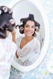 De mooie vrouw in haarkrulspelden zet op ochtendmake-up Royalty-vrije Stock Foto