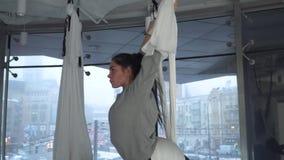 De mooie vrouw hangt in hangmat want de yoga verschillend stelt binnen in studio neemt ityscape achter vloer-aan-plafond stock footage