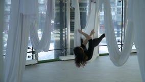 De mooie vrouw hangt in yogahangmat, verschillend stelt nemen in studio Vele witte lege hangmatten rond modern stock videobeelden