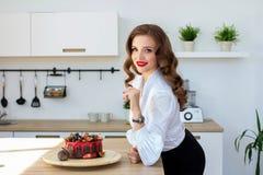 De mooie vrouw heeft cake in keuken gemaakt Stock Foto's