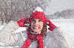 De mooie vrouw heeft een sneeuwbal op een rood GLB stock fotografie