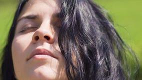 De mooie vrouw heft hoofd tot gevoel op de zon, eenheid met aard, oneness, ogen stock footage