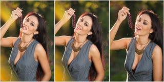 De mooie vrouw in het grijze stellen in herfstpark die rijpe druiven houden bundelt Jonge donkerbruine vrouw die druiven openluch Stock Fotografie