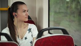De mooie vrouw het luisteren muziek in hoofdtelefoons op smartphone berijdende trein, mooi meisje berijdt een stadsbus stock videobeelden