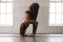 De mooie vrouw het praktizeren yoga, die zich in uttanasana bevinden stelt, door:sturen kromming stock fotografie