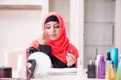 De mooie vrouw in hijab die samenstelling toepassen stock foto's