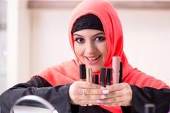 De mooie vrouw in hijab die samenstelling toepassen stock fotografie