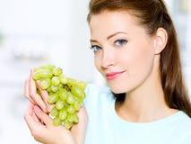De mooie vrouw houdt druiven Stock Foto's