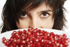 De mooie vrouw houdt granaatappel Stock Foto's
