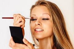 De mooie vrouw houdt samenstellingsborstel en zet op schoonheidsmiddelen op haar gezicht Maak omhoog, schoonheidsmiddelen, schoon stock fotografie