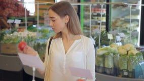 De mooie vrouw kiest binnen alleen tomaten in de supermarkt stock footage