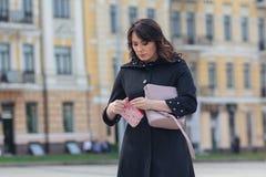 De mooie vrouw kijkt in de zak op een stadsstraat Stock Afbeeldingen