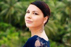 De mooie vrouw kijkt zijdelings, groen maakt achtergrond Royalty-vrije Stock Foto