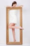 De mooie vrouw in kleding bevindt zich achter groot verguld frame Royalty-vrije Stock Foto