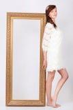 De mooie vrouw in kleding bevindt zich dichtbij groot verguld frame Stock Foto's