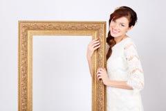 De mooie vrouw in kleding houdt groot verguld frame. Stock Afbeeldingen