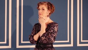 De mooie vrouw in kleding stelt dichtbij muur in blauwe ruimte stock footage