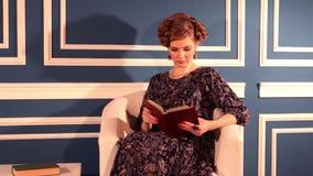De mooie vrouw in kleding zit in blauwe ruimte en leest boek stock video