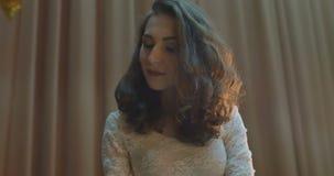 De mooie vrouw in kleding zit op zwarte grote piano stock video