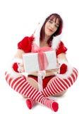 De mooie vrouw kleedde zich als Kerstman zittend op de vloer met pres stock fotografie