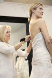 De mooie vrouw kleedde zich omhoog in huwelijkskleding terwijl het hogere eigenaar helpen in bruids opslag Royalty-vrije Stock Fotografie