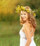 De mooie vrouw in kroon van bloemen ligt uit in het groene gras Royalty-vrije Stock Foto