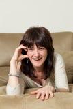 De mooie vrouw lacht openlijk terwijl het liggen op de bank royalty-vrije stock foto's
