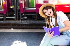 De mooie vrouw leest reishandleiding voor het kijken toerist stock foto's