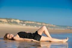 De mooie vrouw legde op snad bij het strand stock afbeeldingen
