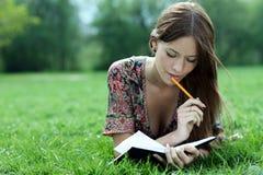 De mooie vrouw legt op een gras in park met een agenda in Ha stock fotografie