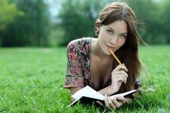 De mooie vrouw legt op een gras in park met een agenda in Ha stock afbeelding