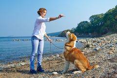 De mooie vrouw leidt haar hond dichtbij overzees op stock foto's