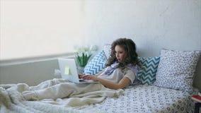 De mooie vrouw ligt in op bed en werkt aan laptop in de ochtend stock video
