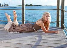 De mooie vrouw ligt op een houten platform over het overzees. Portret in een zonnige dag Royalty-vrije Stock Foto's