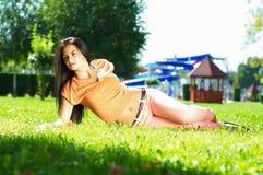 De mooie vrouw ligt op groen gras op zonnige dag in Th Stock Afbeelding