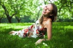 De mooie vrouw ligt op het gras Royalty-vrije Stock Afbeelding